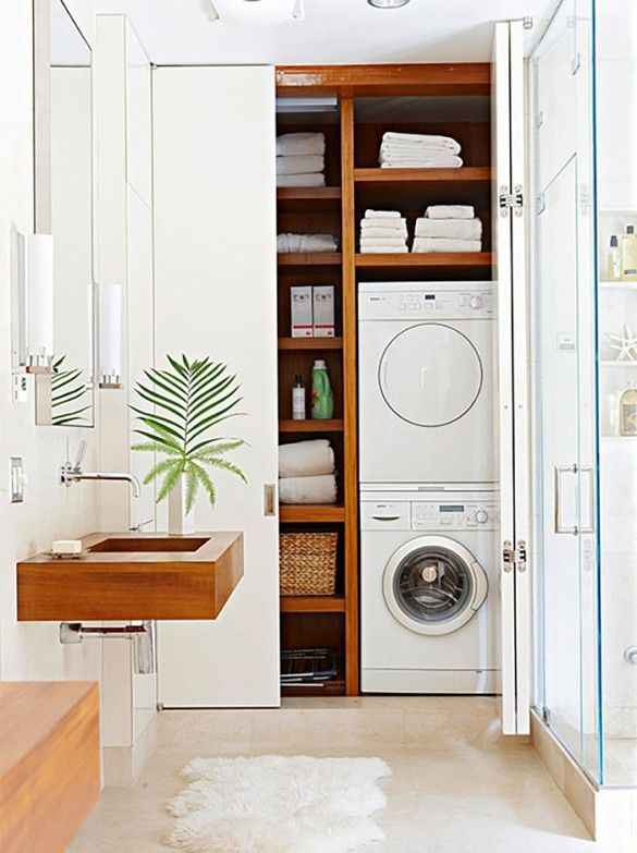 Washer and dryer is hidden in wooden shelving behind white closet, wooden sink, simple plant, side wall lights, and furry rug