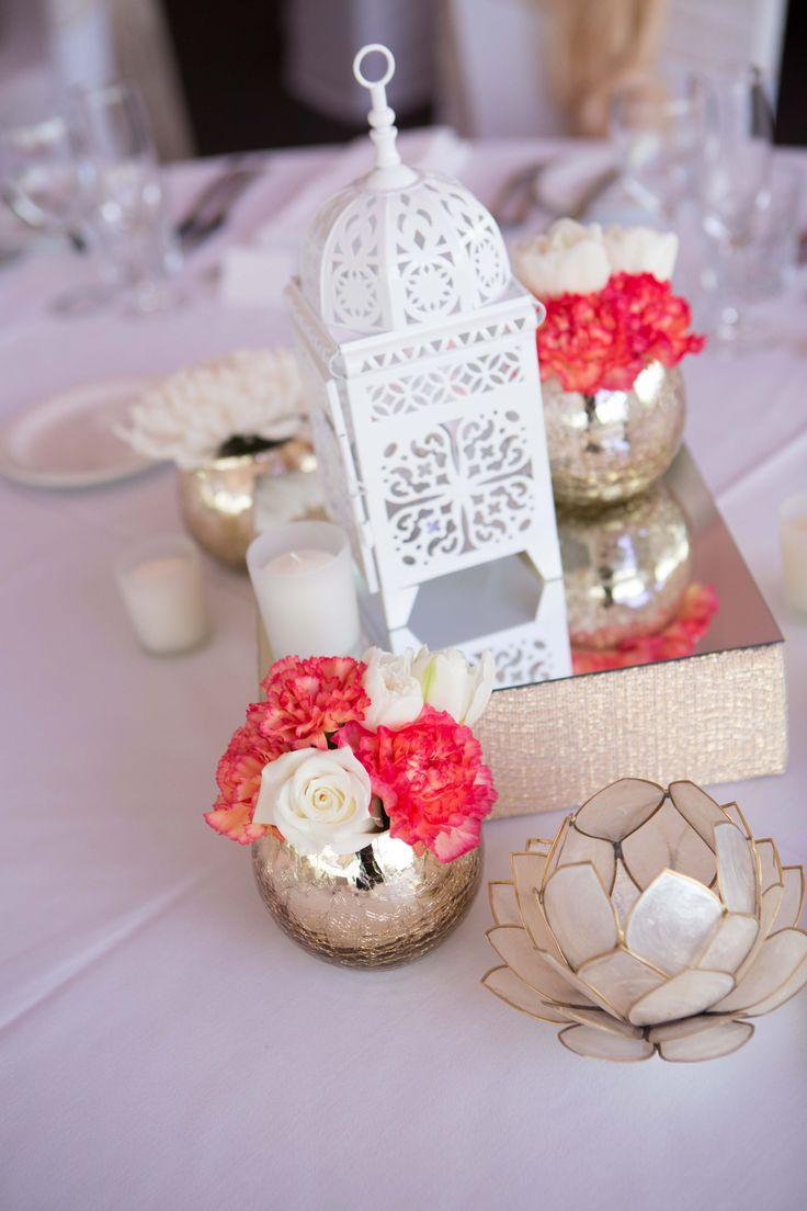 One of our wedding centerpieces / table settings with mercury votive's, a stunning lantern and lotus tea lights. We had two romantic styles for the reception.
