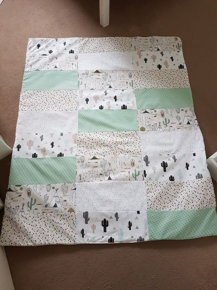 Beautiful baby boys quilt/blanket with jade, white and mixed colours using designs of teepee's, small shapes and cactus. Gorgeously arranged into rectangular patches.