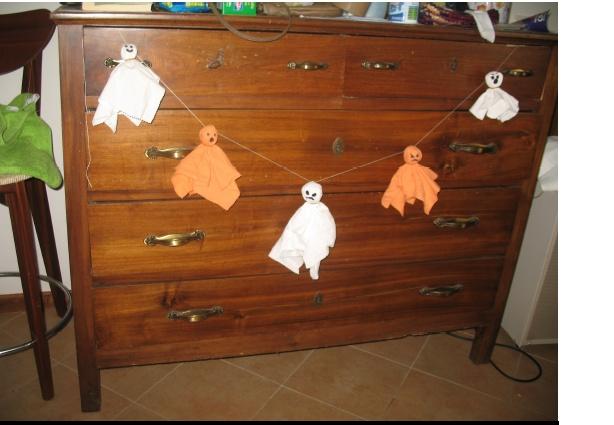 Qualche ritaglio di tela bianca e arancio, carta di giornale, elastici, pennarello, ago e filo: ecco fatta una piccola ghirlanda di fantasmi!