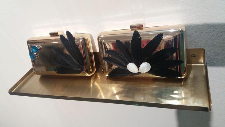 Bolsos en base dorada (disponibles en base plateada) con plumas negras y piedras azules y blancas. ¡Encuéntralos en nuestra tienda de Gijón! #bolsosfiesta #clutch #bolsos #invitadasboda #invitadas #apparentiate #tiendagijon