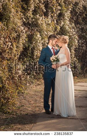 Romantic wedding couple looking at each other and holding bouquet in hands - stock photo