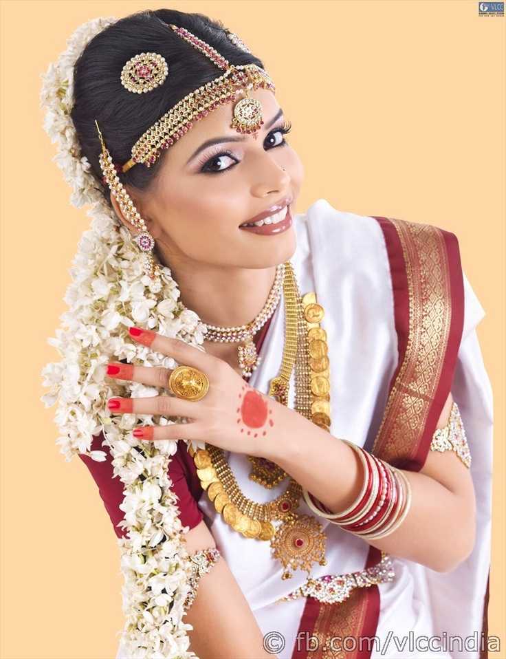 "The natural tan complexion is complimented with silicon or high definition make-up. The eyes are embellished in gold while thick black liner and a generous coat of kohl attract attention. The lips are colored either maroon or bronze. The hair is parted in the middle, then decked up with the traditional Surya and Chandra accessories while ""moggu jade"" adorns the traditional plait."