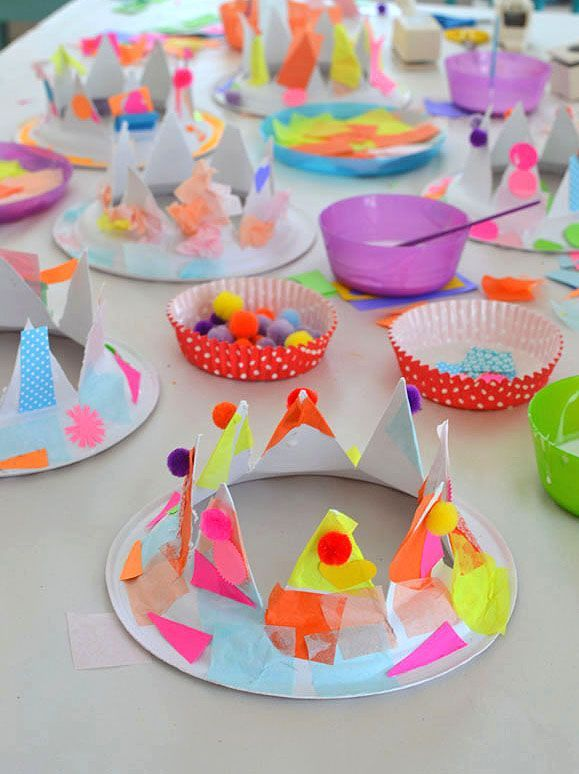 Children use collage materials and pom-poms to decorate paper plates that are cut into party hats.