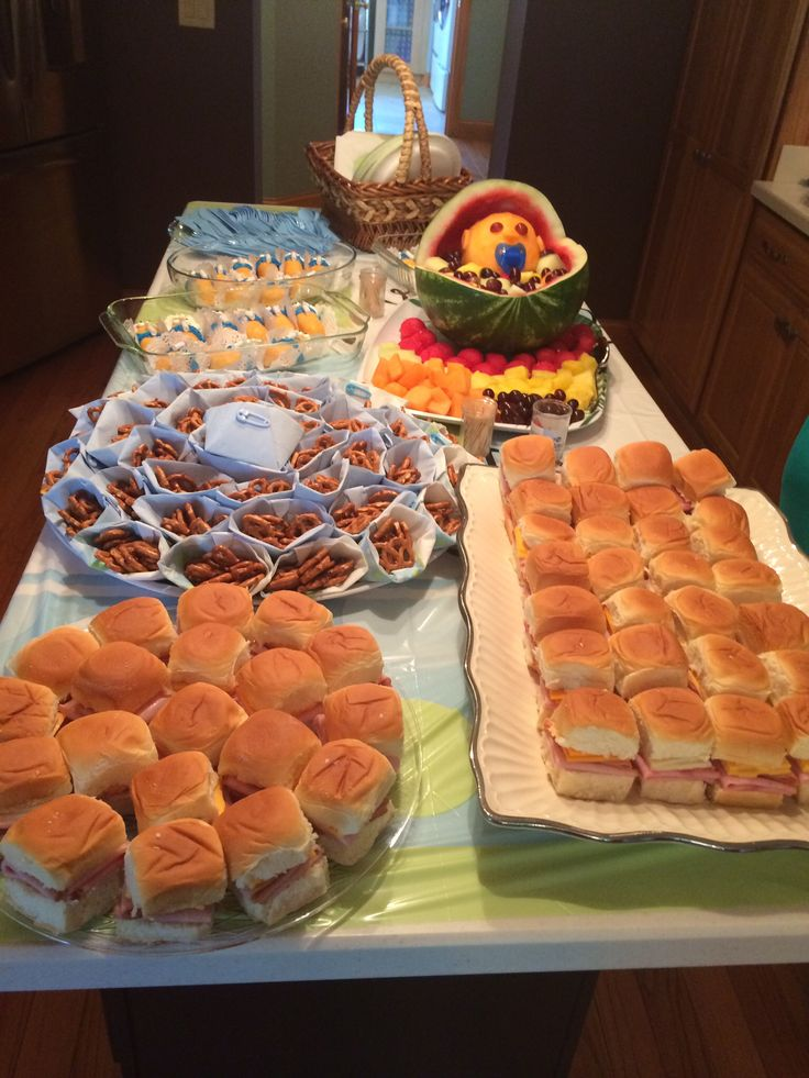 "Baby Shower food on a budget. Sandwiches on Hawaiian rolls, pretzel ""diapers"", baby bassinet fruit bowl, Twinkie babies and blue deviled eggs."