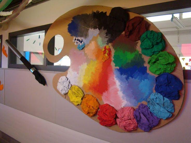 Paleta gegant de colors. Base de cartró i taques de colors amb papers de diaris pintats. Pinzell gegant fet amb tub de cartró de tela de roba.