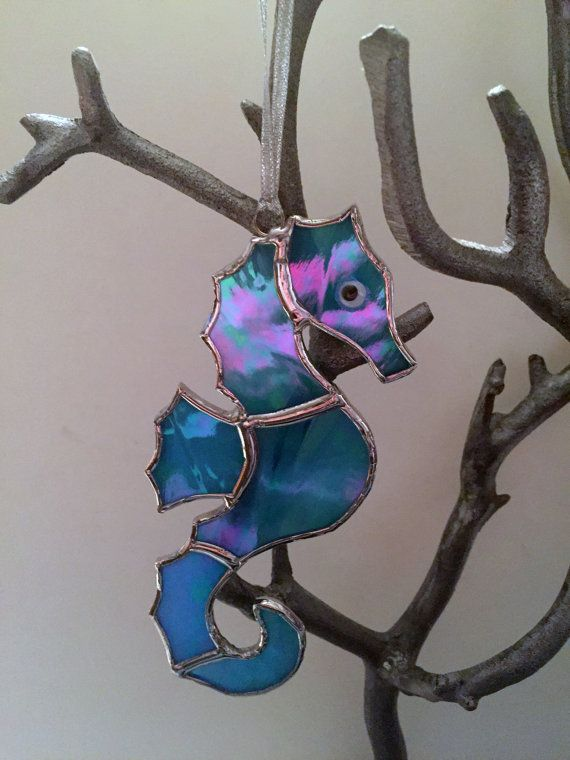 These handmade stained glass seahorse suncatchers/ornaments are perfect for your coastal home or Christmas tree.  Currently available in four colors:  ~ Iridescent Green (only one available) ~ Blue/Green ~ Iridescent Aqua ~ Sandy Beach  If you are interested in a different color, contact me. I can make this in any color you desire.  (Listing is for ONE seahorse.)  Approximately 6.25H x 2.50W  (Suction cup included with all suncatcher purchases.)  NOTE ABOUT SALES TAX: We are require...
