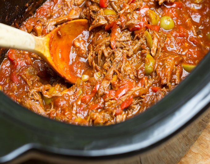 Ropa Vieja is a famously delicious Cuban stew of tender shredded beef with bell peppers, tomatoes, olives and spices. It cooks perfectly in a slow cooker!