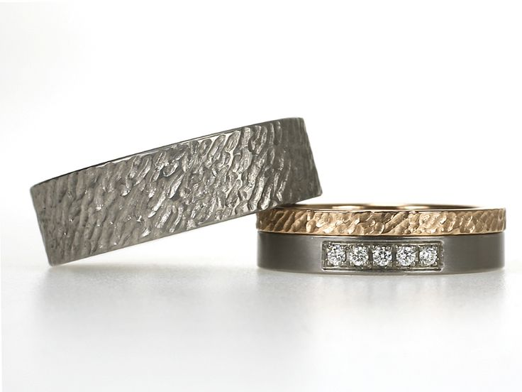 Strandringen in een combinatie van titanium met roodgoud. In de damesring een reeks van 5 diamantjes van 0.015 ct.