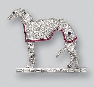 DIAMOND AND NATURAL AND SYNTHETIC RUBY GREYHOUND BROOCH, CIRCA 1930. Modelled in profile standing on a baguette diamond platform, pavé-set throughout with old European-cut and single-cut diamonds, the total diamond weight approximately 6.50 carats, the blanket edged in buff-top calibré-cut natural and synthetic rubies, accented with a calibré-cut sapphire, the eye and nose of onyx, mounted in platinum