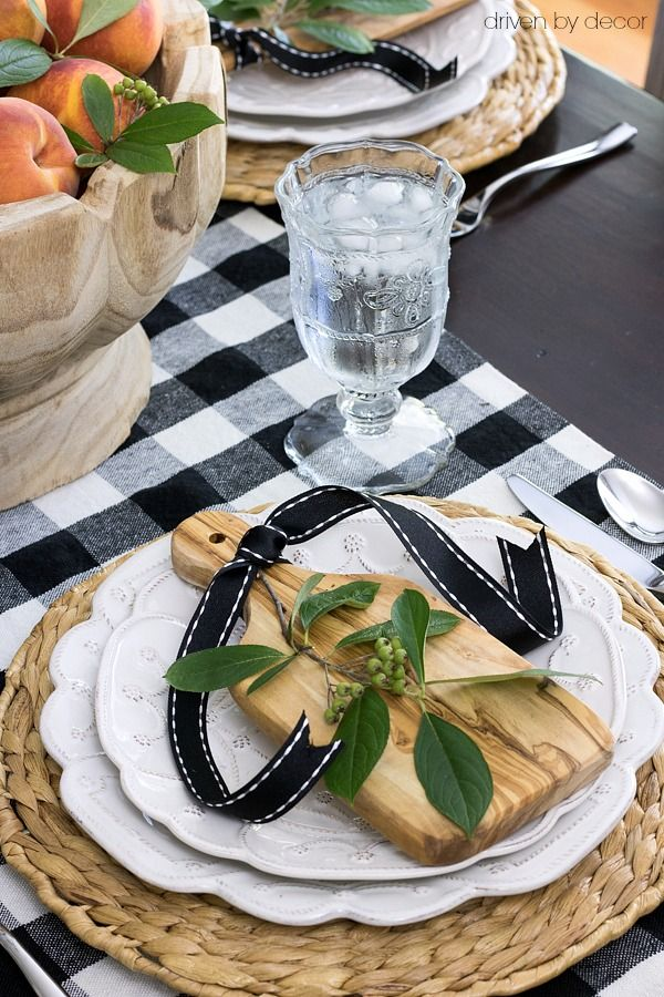 Fall place setting with mini cutting boards (a HomeGoods find!), ribbon, and a sprig of greenery on each plate - part of a full fall home tour! (sponsored pin)