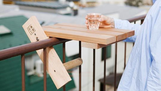 """Cool. Sky Deck table is a mini table designed to """"wrap"""" itself around the rails of balconies or fire escapes, giving you just enough horizontal surface space for a small plate and something refreshing to drink."""