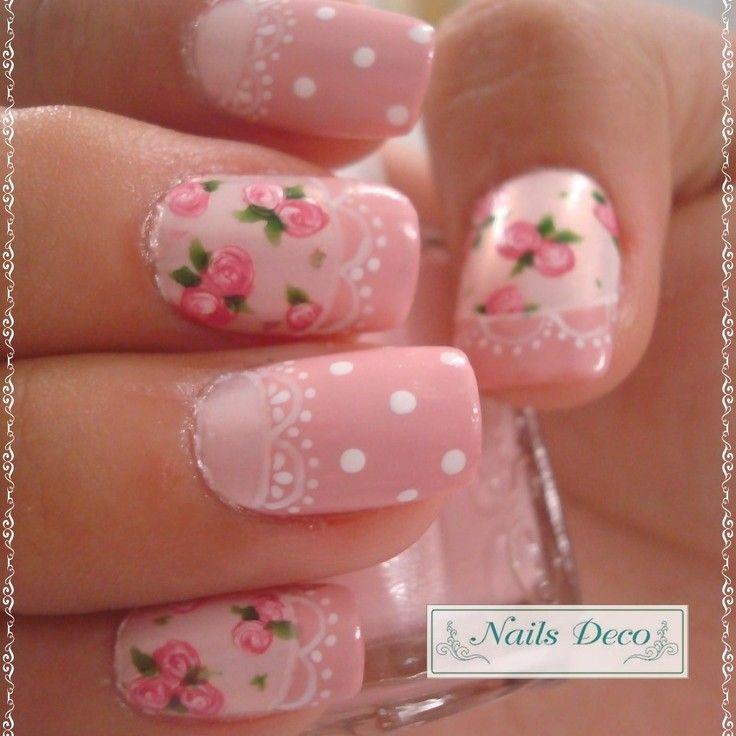 Preciosas uñas en tonos rosa pastel, adornadas con lunares blancos, diseños de flores rosas y hojas verdes, también cenefas y lunares blancos.