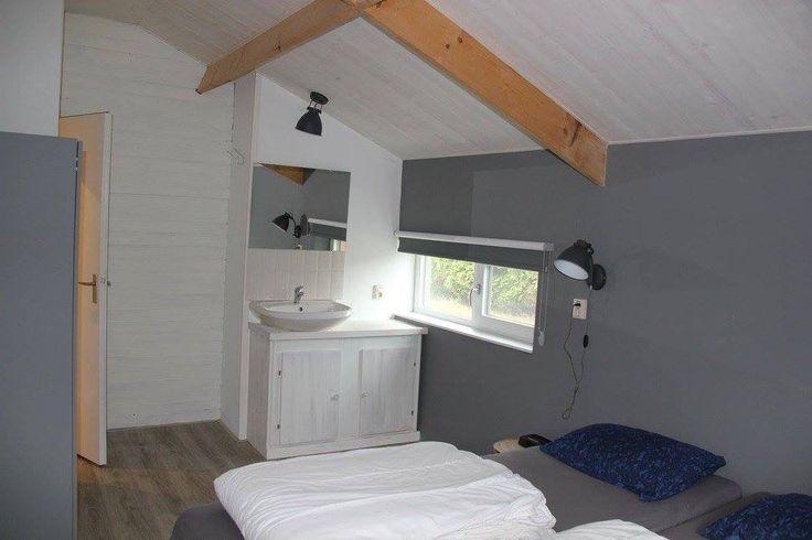 Wastafel gemonteerd op wit geschilderd kastje. Donkergrijze muren met stoere wand en plafondlamp Slaapkamer vakantiehuis Oostkapelle