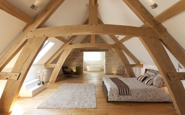 Upper cruck style trusses form an elegant master bedroom.  Storey and a half style framing brings an intimate feel to the oak frame carpentry within the room. (Photography: Duncan McNichol)