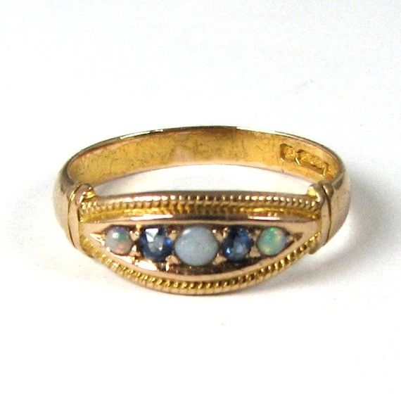 Looks like opal, sapphire, and moonstone in a gold band, I love this.