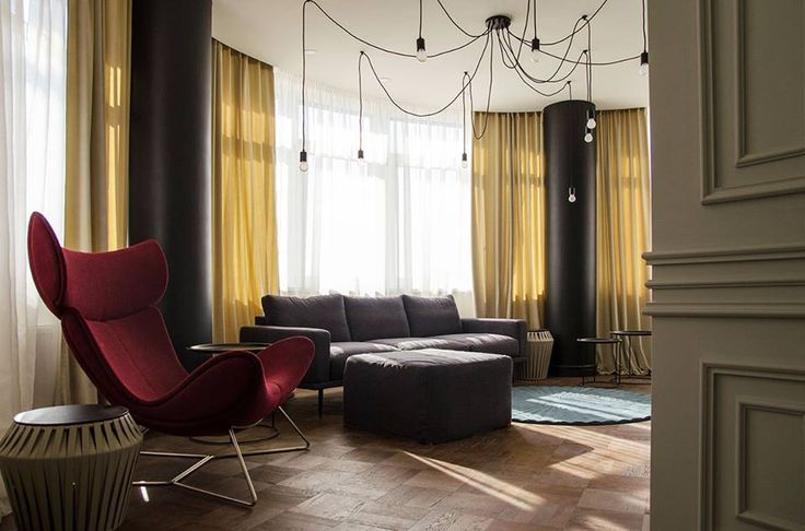Living room with red armchair grey sofa and round blue carpet. Yellow curtains, dark wood parquet, grey walls #SMIRNOVAINTERIORSPARIS