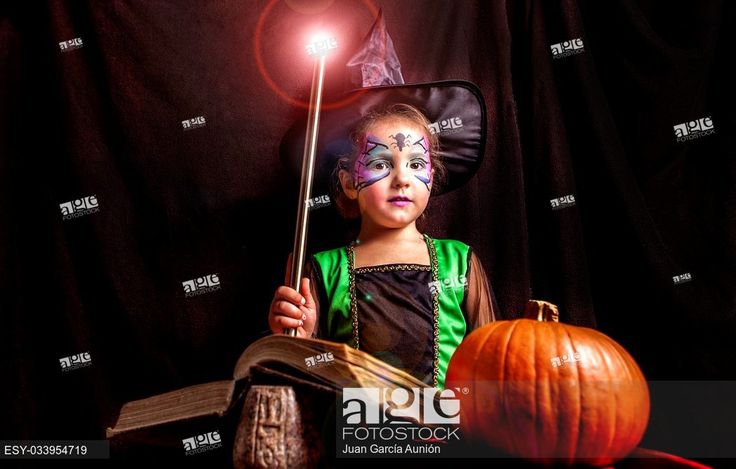 Stock Photo: Little cute girl costumed as a witch reads the Book of Spells. Studio take.