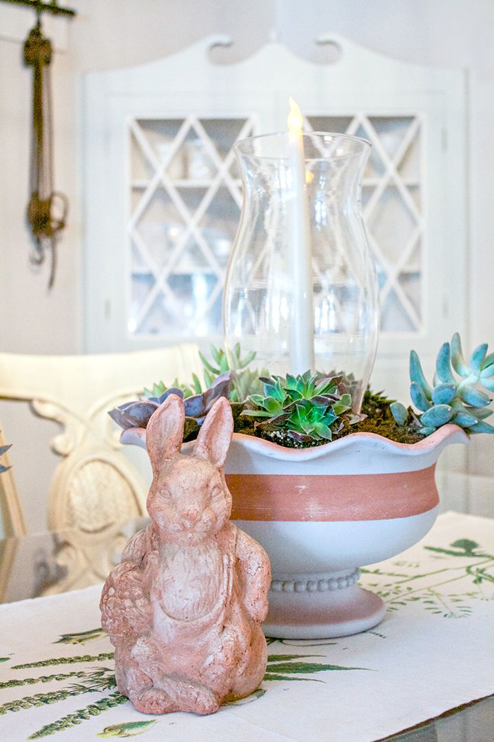 Painted flower pot with a plant and candle in it with a bunny ornament positioned next to it