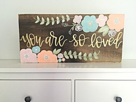 Size: 24 wide by 12 tall Details: This listing features a stained wood background with lightly distressed edges. Hand painted flowers featured in mint, coral, and blush pink with gold and white accents and gold hand painted lettering featuring the quote you are so loved Options: We would be more than happy to create a custom version of this sign for you! Include your details at checkout in the notes area or message us prior to ordering to discuss your ideas! *Hanging hardware not included…