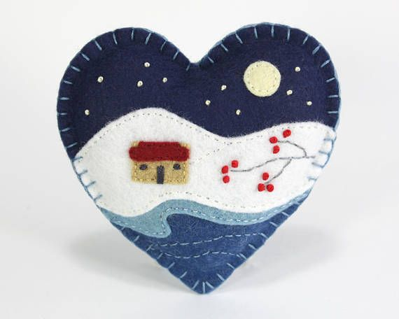 A handmade felt Christmas heart ornament, embroidered with a traditional Irish cottage in a snowy winter landscape, under a full moon and starry night sky. The heart measures approx. 4 inches / 10cm across, and has a cotton loop for hanging. You can see other variations on this
