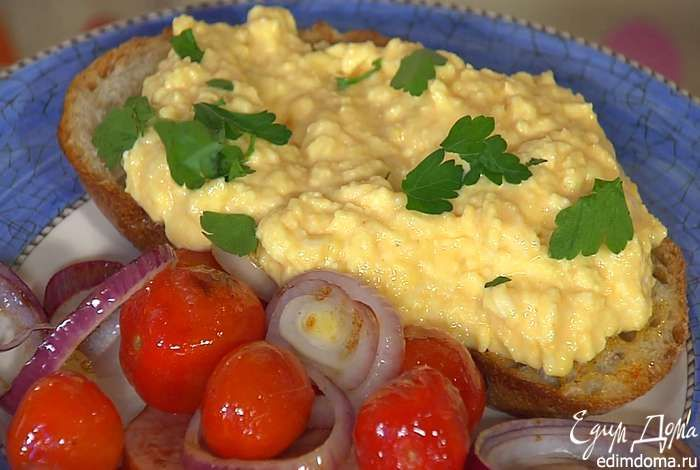 На обжаренный хлеб выложить яичную массу и посыпать измельченной руками петрушкой. Подавать обжаренный хлеб с помидорами, колбасой и луком.