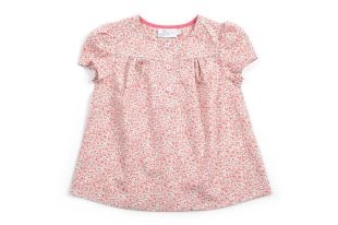 Blusa para niña en tela estampada con florectias rojas. Cuello redondo y mangas cortas.