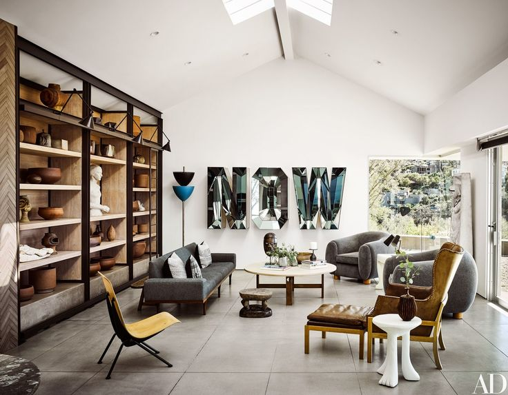 In the living room, decorated by Cliff Fong of Matt Blacke Inc., a Doug Aitken mirrored artwork reflects a mix of midcentury furnishings.