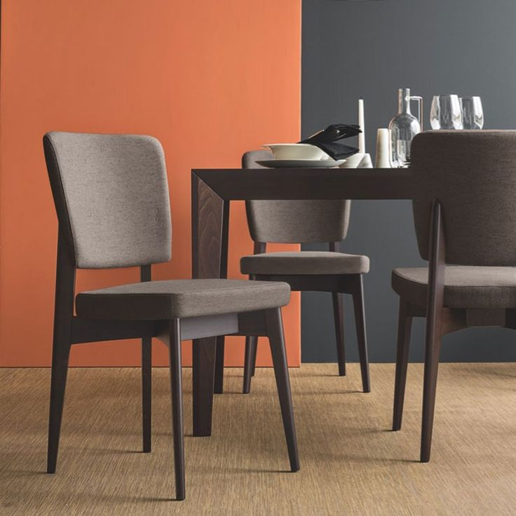 The Connubia Calligaris Escudo Chair in faux leather has a mid-century wooden frame and a comfortable curved backrest; designed to suit cool modern homes.