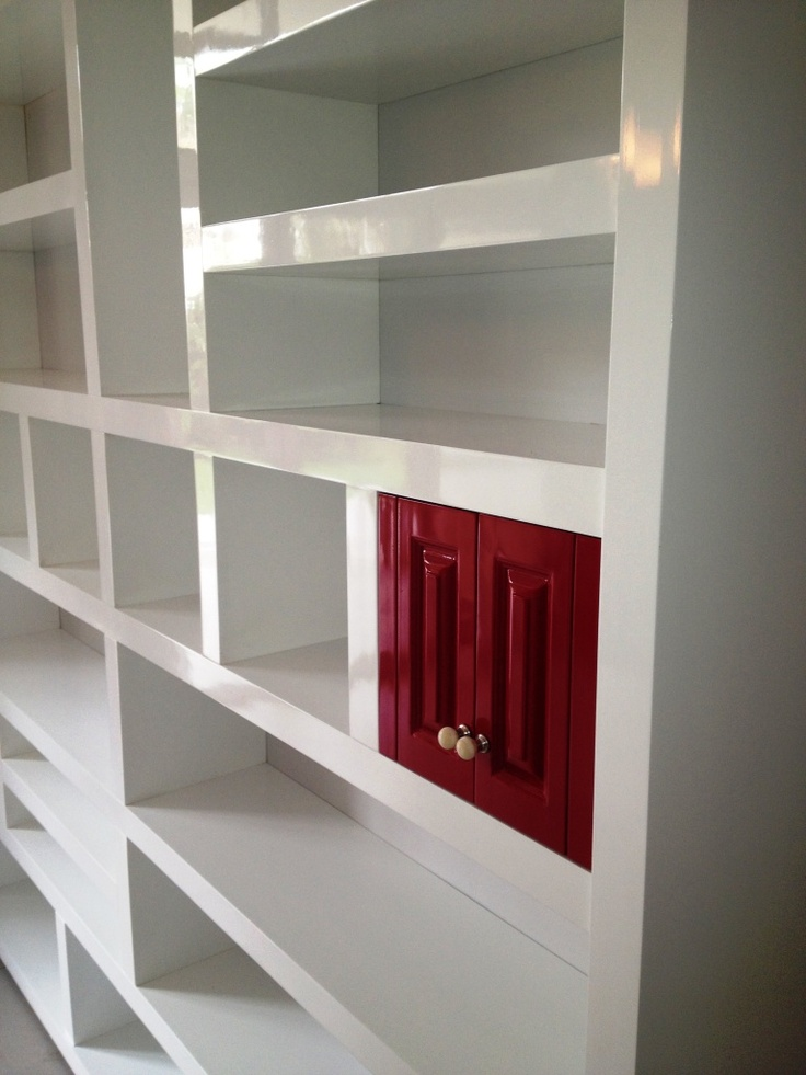 Duco sprayed white bookcase with little red doors.