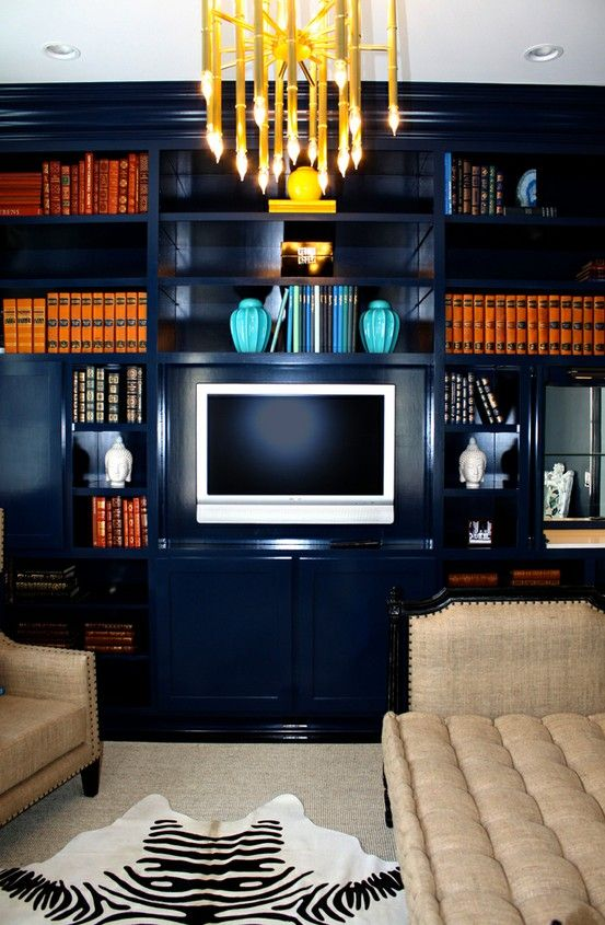 navy/orange: Living Rooms, Yellow Chandeliers, Bookshelf Wall, Color, Navy Wall, Families Rooms, The Navy, Leather Books, Entertainment Center