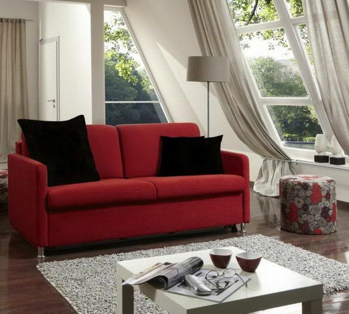 curtains for living room, red sofa with black cushions, small white table, several windows some with pale cream curtains