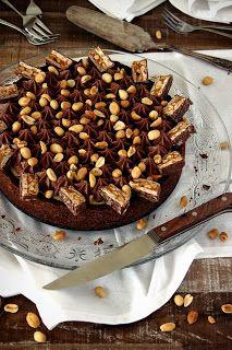 Snickers cheesecake 250 g digestive biscuitjes 150 g boter 230 g fijne kristalsuiker 34 g cacaopoeder snufje zout 1 vanillestokje 850 g roomkaas 20 g bloem 90 ml slagroom 2 eidooiers 2 eieren 125 g Snickers + extra voor garnering 60 g zoute pinda's + extra voor garnering 100 g poedersuiker 3 g vanillesuiker