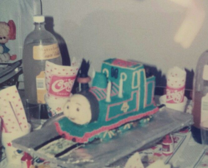Thomas the Tank Cake Sponge cake cut and shaped with coloured  butter icing over. Track painted on board. 1988