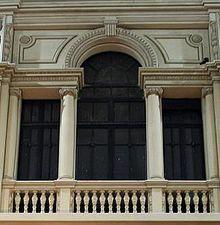 SERLIANA - PALADIANA: es el nombre de un recurso arquitectónico muy utilizado en el Renacimiento y posteriormente en el periodo neoclásico, que consiste en combinar arcos de medio punto con vanos adintelados. Debe su nombre al arquitecto Sebastiano Serlio, que fue el primero en teorizar sobre esta forma arquitectónica. La serliana se utiliza generalmente en portadas y loggias a modo de arco de triunfo en el que los laterales están adintelados y son más bajos.