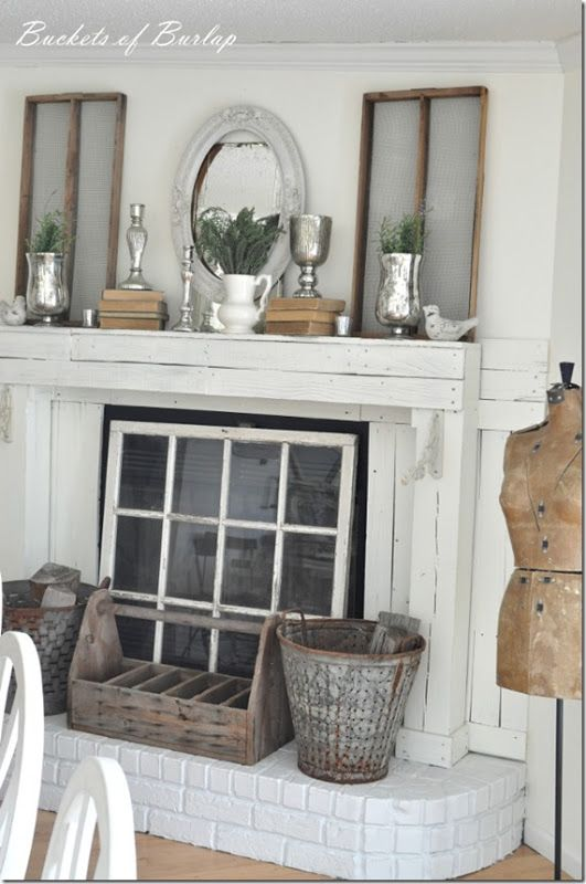 Love the old window to cover the fireplace, and the silver accents are nice with all the rusticness