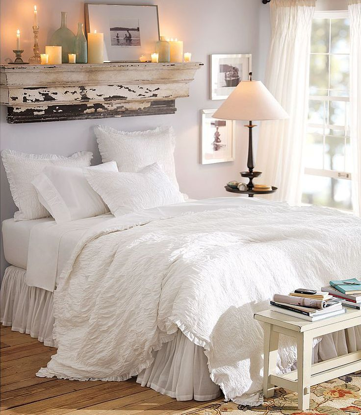 Too feminine, but the re-purposed wood with candles and white linens with a table at the base of the bed are ideas.