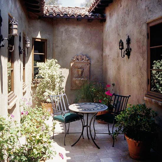 Create Old-World Style with Sconces - Wrought-iron sconces bring a touch of Tuscany to this sliver of an outdoor room. Choosing light fixtures with the same finish as the door pulls, fencing, and outdoor furniture gives your outdoor rooms a professional, pulled-together look