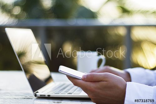a man working with a laptop and cell phone at sunrise