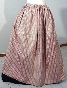 Förkläde så kallat bladförkläde vävt i 12 skaft. Vit botten med mönster av blåa blad samt rött och blått punktmönster. Knytband av samma tyg. Från Kristianopel