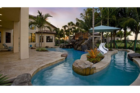 The pool of the Bassano model from GL Homes wraps around a stone planter and bridge, sheltered by tall palms. The Bridges community. Delray Beach, FL.