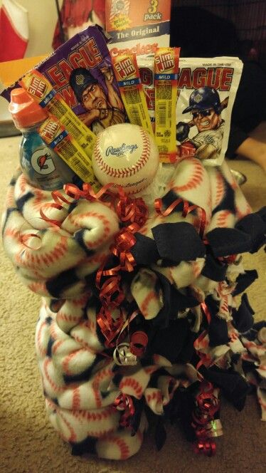 Baseball themed gift.  I made a tie blanket. In the middle i rolled a gatorade sunflower seeds and a foam block. On the bottom i used a cardboard square to hold it all up. Than tape the items to popsicle sticks (i used two for the baseball) and place them as you wish in the foam. I had cracker jacks, big league chew, slim jims, a baseball in the foam.
