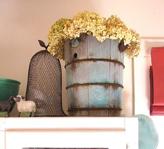 How about repurposing an old ice cream maker bucket into a vase - the dried hydrangeas are a perfect delicate foil to the structure of the wood.
