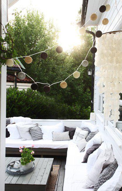 terrasse gestalten in garu und weiß mit kugelleuchten und DIY couchtisch holz