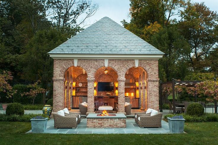 Gorgeous patio features a brick pool house accented with arched entrances fitted with a kitchen boasting stainless steel cabinets paired with black stone and a red brick herringbone backsplash.