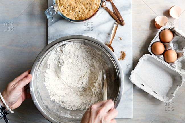 Mixing flour in bowl for hot cross buns close-up, Mixing hot cross bun dough close-up,  hot cross buns, baking, freshly baked buns, butter, homemade, oven tray, glazed hot cross buns, mixing batter, flour and butter mixture, batter mixture, mixing bowl,topshot,