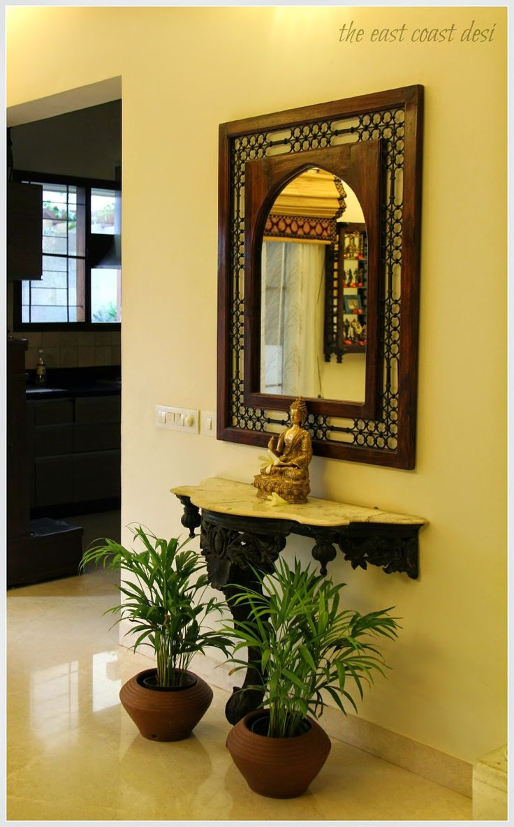 A marble top carved pedestal console with an ornate metal engraved mirror from Saharanpur. A serene looking brass Buddha and fresh palms in terracotta pots bring this corner alive