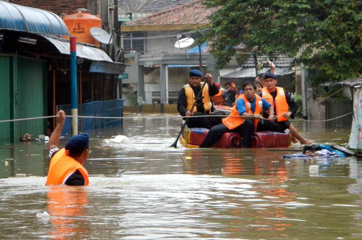 A rescue team looks for people stuck in their homes in a flooded area of Jakarta on January 18, 2013. Floods in Indonesia's capital Jakarta have left at least 11 people dead, authorities said on Friday as murky brown waters submerged parts of the city's business district, causing chaos for a second day | © Bay Ismoyo | AFP Photo