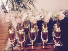 Cheap and easy center pieces for a 1920s themed party or any occasion! Customize your own colors!  Recycled wine bottles $0 (soak overnight to get label off and scrape with razor blade), Gold Spray paint $5 at the hardware store, Plastic pearl necklaces 12 for $7 on shindigz.com, Pink roses (25 roses)  for $10 flower district downtown LA and one bunch baby's breath $3, white feathers one per bottle $5 on Amazon.com pack of 22.  Each center piece cost me $2.50/ea! Steal!
