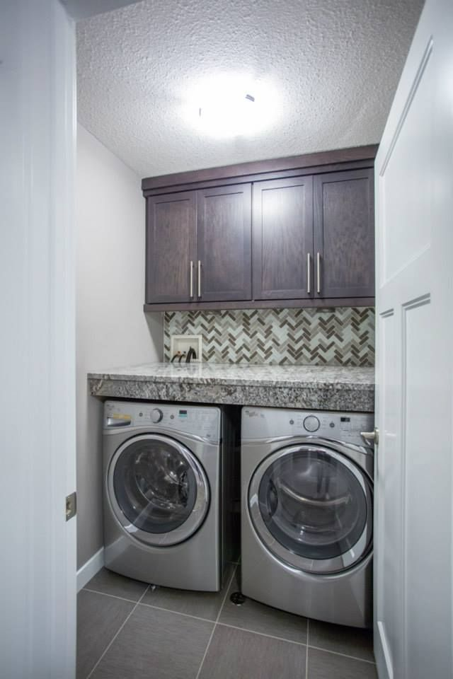 Laundry room with side by side washer and dryer. complete with counter space and cabinet space. Check out that backsplash